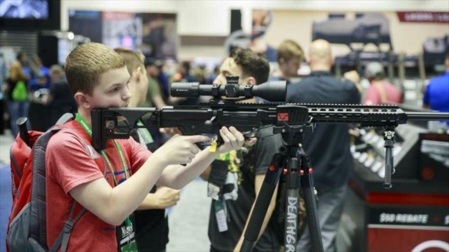 Un estudiante examina un fusil durante una exposición de la NRA en un colegio en la cuidad de Indianópolis en centro-este de EE.UU.