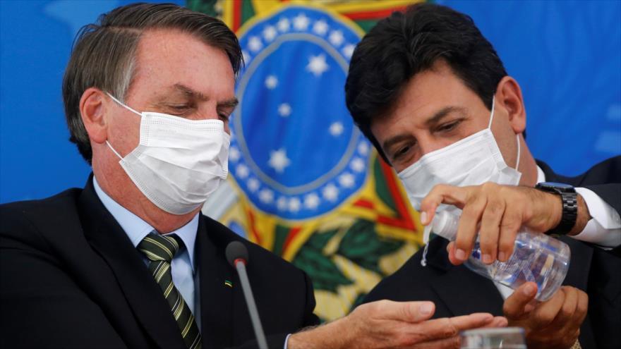 El presidente brasileño, Jair Bolsonaro (izqda.), y el exministro de Salud del país Luiz Henrique Mandetta. (Foto: AFP)